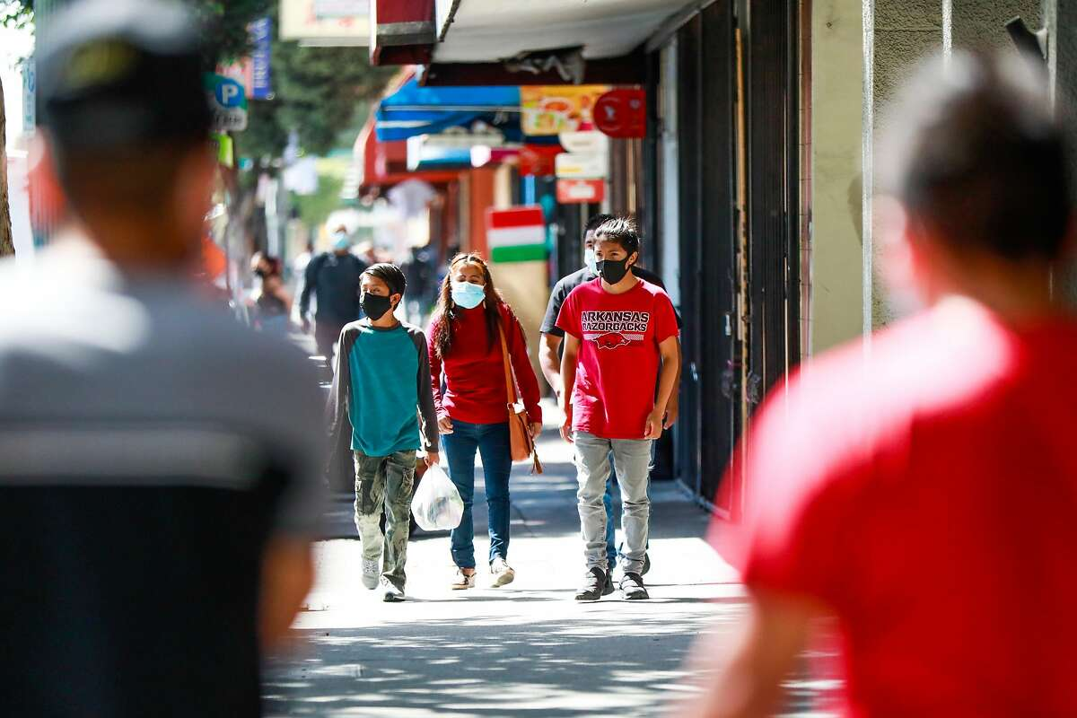 People wear masks as they walk on International Boulevard in the Fruitvale area of Oakland, California on Sunday, June 28, 2020.