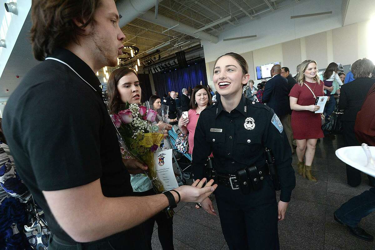 Beaumont Police officer Sheena Yarbrough talks with her boyfriend Tyler Powell, who brought flowers to congratulate her after joining 11 others sworn into office during a milestones ceremony Tuesday at the Event Centre. Twelve new officers were sworn in, officer Cody Foote was recognized for his promotion to Sergeant, and other officer and civilian awards were presented during the event. Photo taken Tuesday, January 8, 2019 Photo by Kim Brent/The Enterprise
