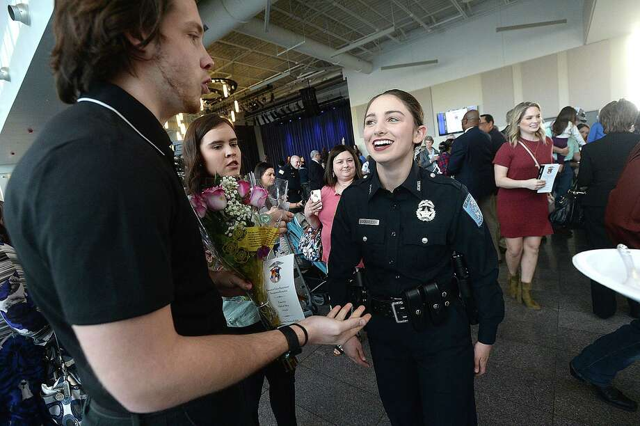 Beaumont Police officer Sheena Yarbrough talks with her boyfriend Tyler Powell, who brought flowers to congratulate her after joining 11 others sworn into office during a milestones ceremony Tuesday at the Event Centre. Twelve new officers were sworn in, officer Cody Foote was recognized for his promotion to Sergeant, and other officer and civilian awards were presented during the event.  Photo taken Tuesday, January 8, 2019  Photo by Kim Brent/The Enterprise Photo: Kim Brent / The Enterprise / BEN