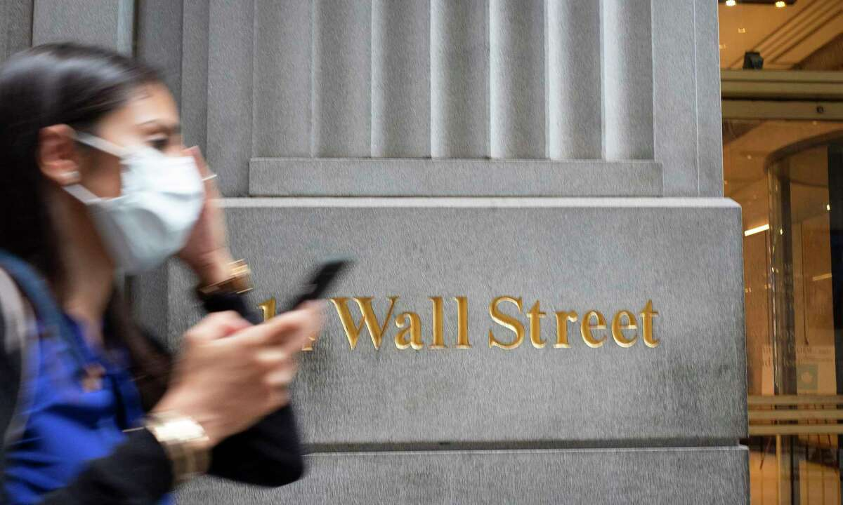 FILE - In this June 30, 2020 file photo, a woman wearing a mask passes a sign for Wall Street during the coronavirus pandemic. Stocks are opening higher on Wall Street, pushing the S&P 500 ever closer to the all-time high it reached back in February, before the coronavirus shutdowns slammed the economy. The index was up 0.3% in the early going Tuesday, Aug. 11. (AP Photo/Mark Lennihan, File)