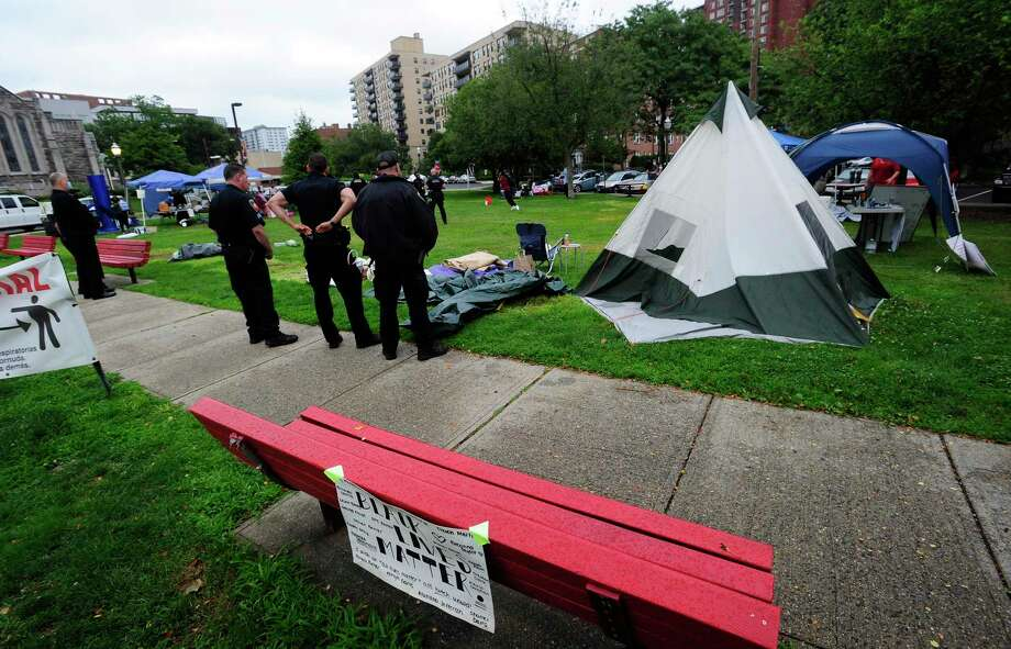 Stamford Police monitor the scene as protesters pack up and breakdown an encampment at Latham Park on July 17, 2020 in Stamford, Connecticut. Photo: Matthew Brown / Hearst Connecticut Media / Stamford Advocate