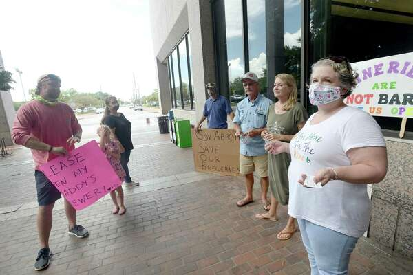 Owners of local breweries and wineries (from left) Tyler Blount, Raegan and Joel Hollier, Clay and Stacy Rollins and Traci Tucker, talk after gathering with signs pressed to the windows of the jury impaneling room at the Jefferson County Courthouse to voice their protest of Governor Greg Abbott's restrictions on their businesses as Abbott held a press conference with local leaders to discuss the status of COVID-19 cases in the area, testing, and other issues. Photo taken Tuesday, August 11, 2020 Kim Brent/The Enterprise