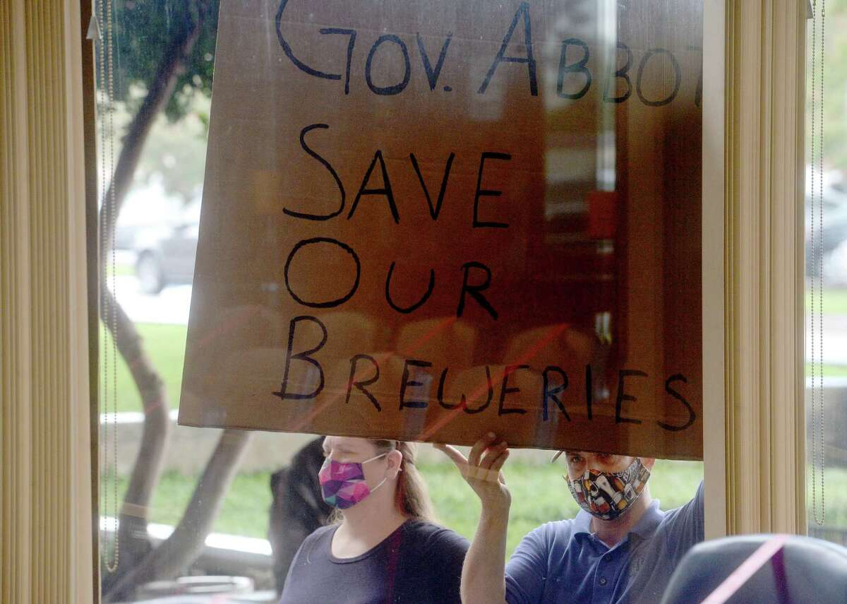 Owners of local breweries, including Raegan and Joel Hollier, and wineries gathered with signs pressed to the windows of the jury impaneling room at the Jefferson County Courthouse to voice their protest of Governor Greg Abbott's restrictions on their businesses as Abbott held a press conference with local leaders to discuss the status of COVID-19 cases in the area, testing, and other issues. Photo taken Tuesday, August 11, 2020 Kim Brent/The Enterprise