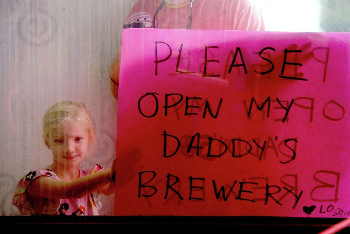 Logan Blount holds a sign for her father Tyler Blount, owner of Neches Brewing Co., as owners of local breweries and wineries gathered with signs pressed to the windows of the jury impaneling room at the Jefferson County Courthouse to voice their protest of Governor Greg Abbott's restrictions on their businesses as Abbott held a press conference with local leaders to discuss the status of COVID-19 cases in the area, testing, and other issues. Photo taken Tuesday, August 11, 2020 Kim Brent/The Enterprise