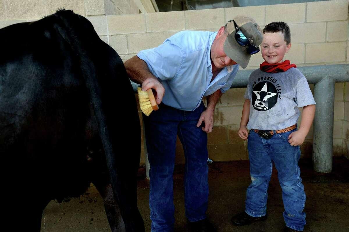 Darren Baxley helps his son Harold, 8, wash his heifer