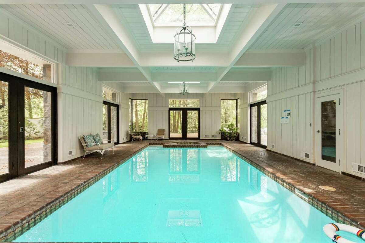 """Among its many luxurious and recreational amenities is an indoor swimming pool, spa and steam room. There is also an outdoor tennis court (not pictured). """"The (9,360-square-foot) main house, guest house, river house and greenhouse combine to offer a sleek, sexy sanctuary with places and spaces for everyone you love. Imagine being together while having the room for when you must be apart,"""" says the listing agent, making reference to social distancing because of COVID-19. According to the agent, this estate, with its 17-room cream-colored Mediterranean-style house and its nearly three-acre waterfront property in the Coleytown neighborhood, influenced The Beatles and perhaps one of the Gershwin brothers, Ira, as well as his sister Frances Godowsky. Frankie, as she was known, was a singer who took up painting after moving to this estate, shortly after her famous brother George died in 1937."""