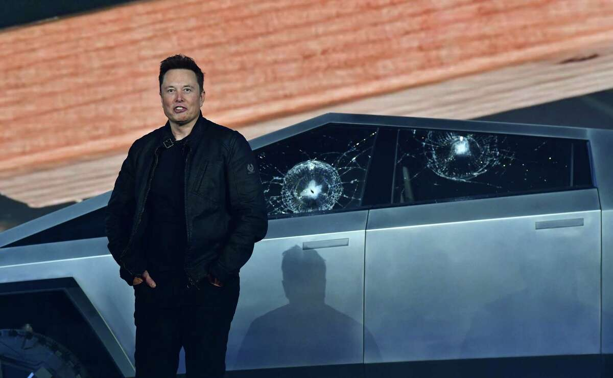 (FILES) In this file photo taken on November 21, 2019, Tesla co-founder and CEO Elon Musk stands in front of the shattered windows of the newly unveiled all-electric battery-powered Tesla's Cybertruck at Tesla Design Center in Hawthorne, California. (Photo by FREDERIC J. BROWN / AFP) (Photo by FREDERIC J. BROWN/AFP via Getty Images)