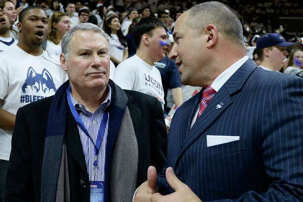 AAC Commissioner Mike Aresco, left, talks with UConn athletic director David Benedict, in 2017. Aresco said the AAC will go ahead with its football season.