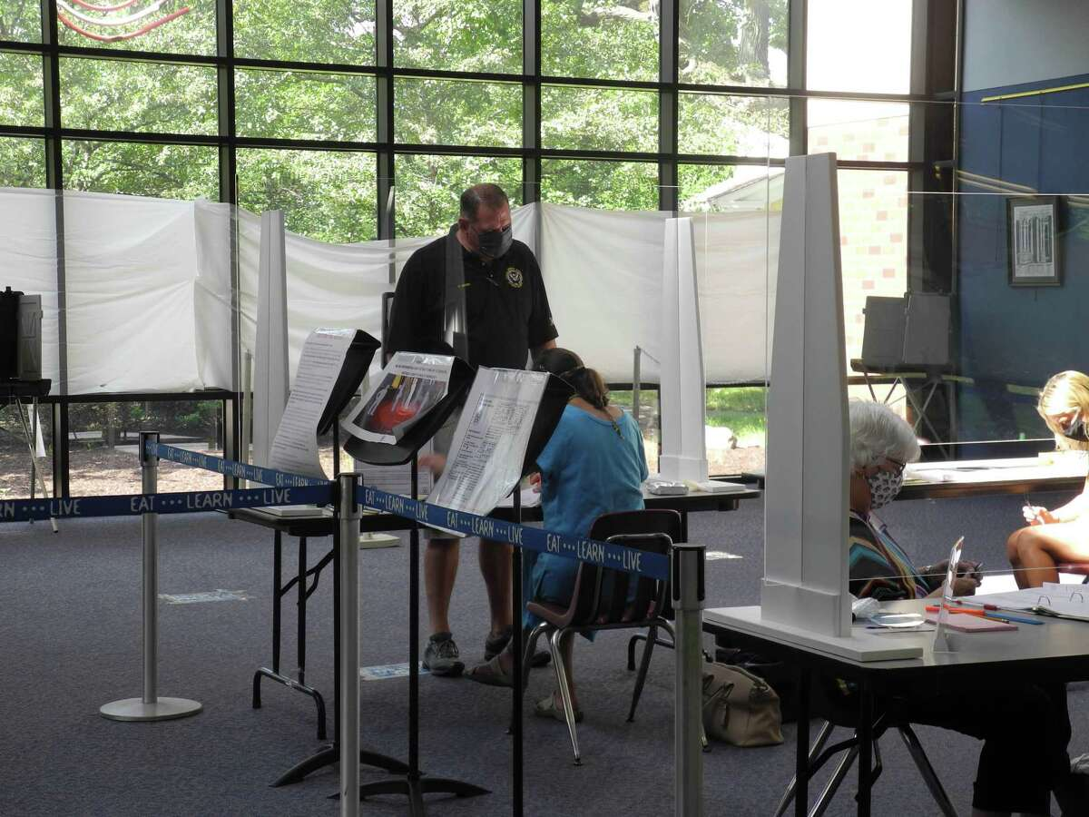 A voter checks in at the polling place at Wilton High School on Aug. 11.