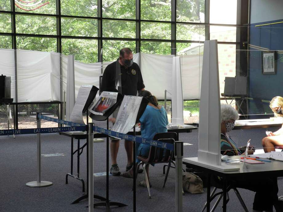 A voter checks in at the polling place at Wilton High School on Aug. 11. Photo: Jeannette Ross / Hearst Connecticut Media / Wilton Bulletin