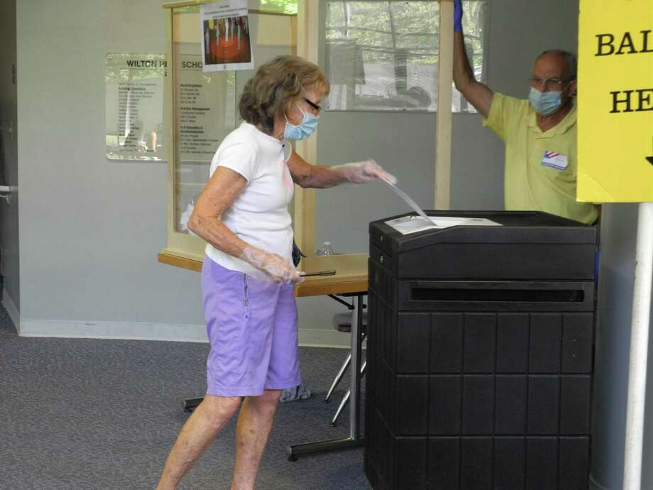 A woman votes at the polling place at Wilton High School on Aug. 11, 2020. Photo: Jeannette Ross / Hearst Connecticut Media / Wilton Bulletin