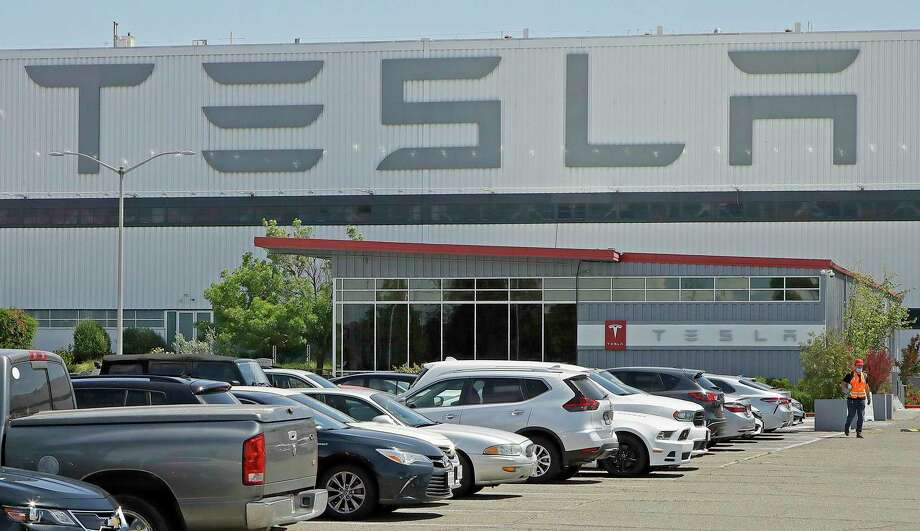 FILE - In this Monday, May 11, 2020 file photo, a man wearing a mask walks through the Tesla plant parking lot in Fremont, Calif. On Wednesday, July 22, 2020, the electric car maker announced it has picked the Austin, Texas, area as the site for its largest auto assembly plant employing at least 5,000 workers. (AP Photo/Ben Margot) Photo: Ben Margot, STF / Associated Press / Copyright 2020 The Associated Press. All rights reserved.