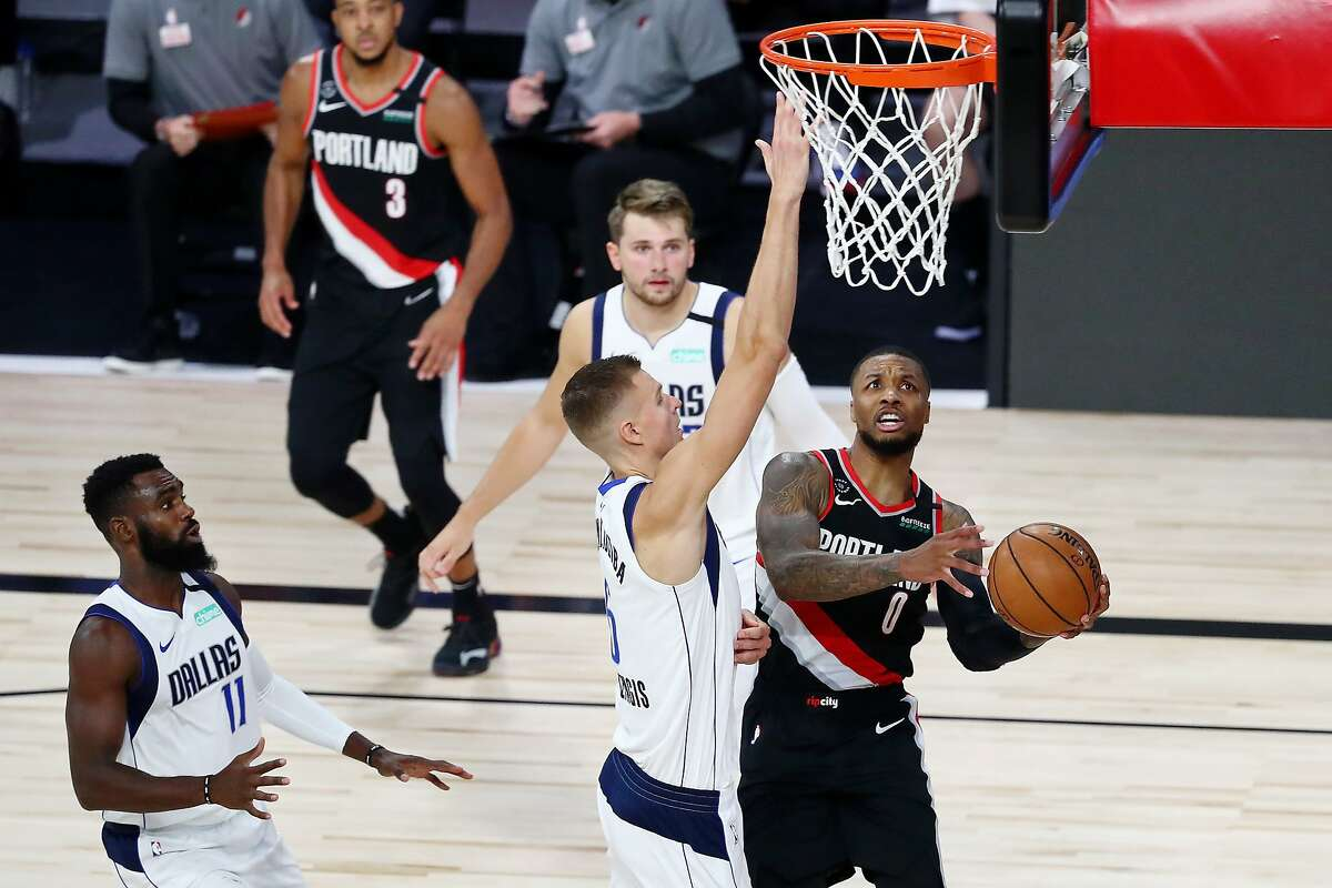 LAKE BUENA VISTA, FLORIDA - AUGUST 11: Damian Lillard #0 of the Portland Trail Blazers drives to the basket against Kristaps Porzingis #6 of the Dallas Mavericks during the second half at The Field House at ESPN Wide World Of Sports Complex on August 11, 2020 in Lake Buena Vista, Florida. NOTE TO USER: User expressly acknowledges and agrees that, by downloading and or using this photograph, User is consenting to the terms and conditions of the Getty Images License Agreement. (Photo by Kim Klement - Pool/Getty Images)