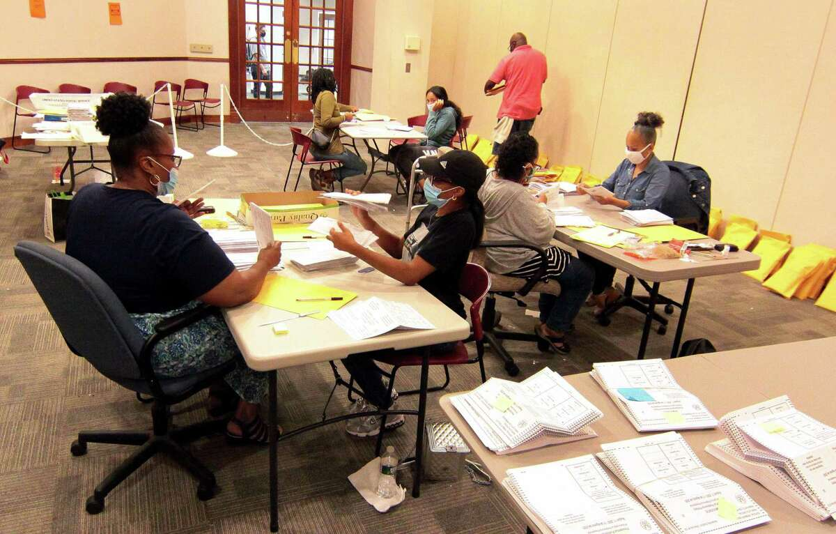 Workers count absentee ballots for the democratic side during the primary election at the Margaret E. Morton Government Center in Bridgeport, Conn., on Tuesday Aug. 11, 2020.
