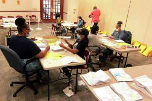 Workers count absentee ballots at the Margaret E. Morton Government Center in Bridgeport on Tuesday.