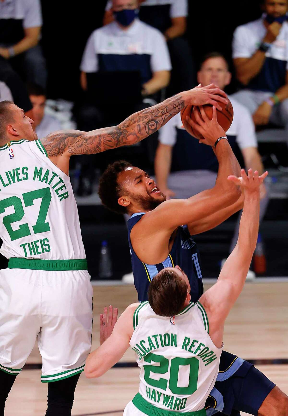 Kyle Anderson, center, of the Memphis Grizzlies', tries to shoot the ball as Daniel Theis, left, of the Boston Celtics and Gordon Hayward, right, of the Boston Celtics defend during the first quarter