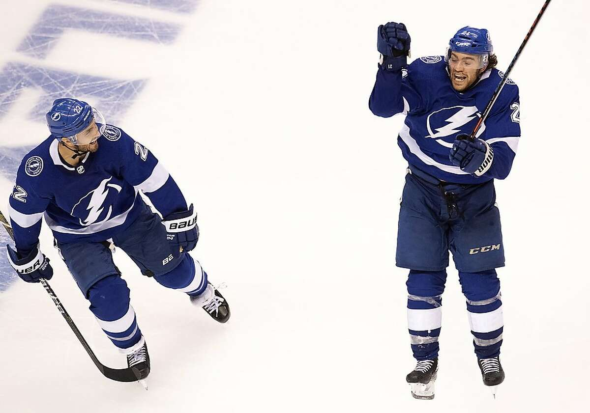 Tampa Bay Lightning center Brayden Point (21) celebrates his game winning goal against the Columbus Blue Jackets with teammate Kevin Shattenkirk (22) during the fifth overtime period in Game 1 of an NHL hockey Stanley Cup first-round playoff series, Tuesday, Aug. 11, 2020, in Toronto. (Frank Gunn/The Canadian Press via AP)