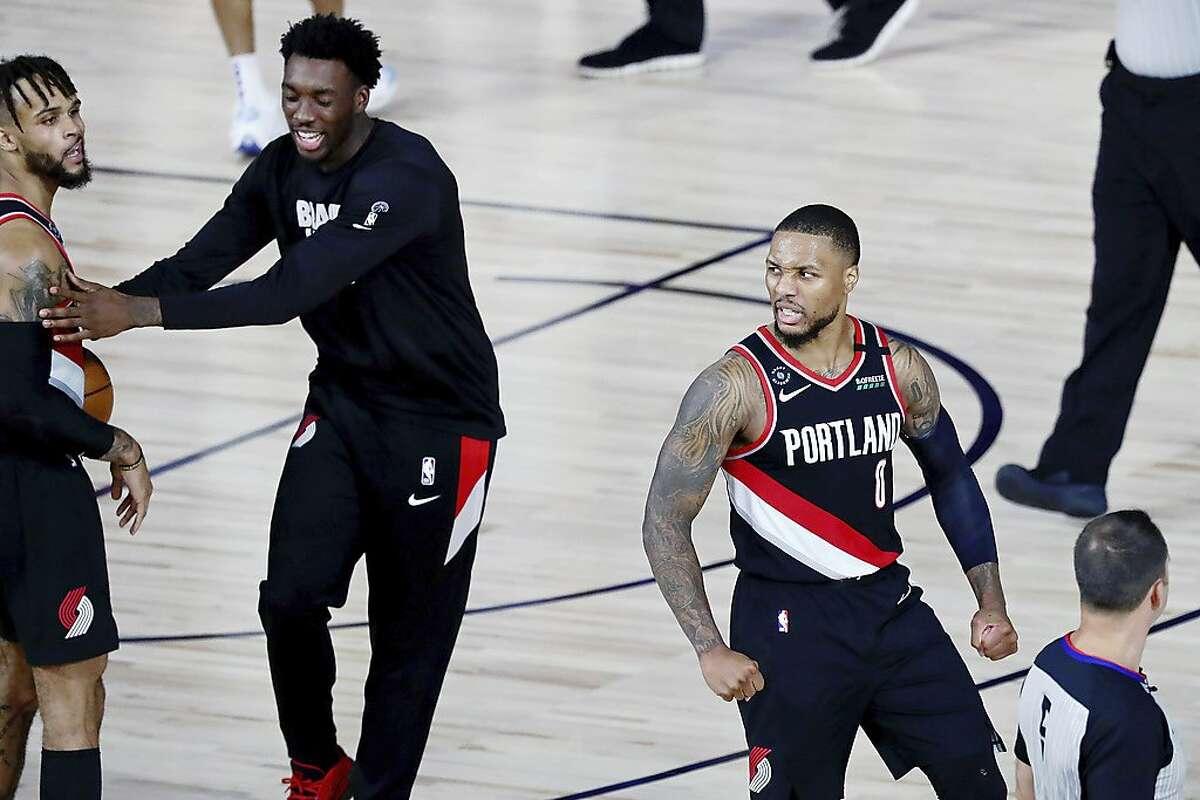 Portland Trail Blazers guard Damian Lillard (0) celebrates after their win over the Dallas Mavericks in an NBA basketball game Tuesday, Aug. 11, 2020, in Lake Buena Vista, Fla. (Kim Klement/Pool Photo via AP)