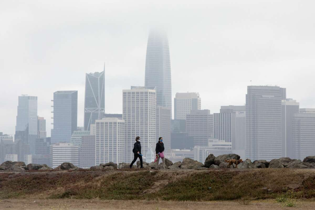 Two people go out for a walk along a pathway at the edge of Treasure Island in San Francisco, California on Aug. 11, 2020.