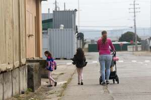 A family walks along one of the streets on Treasure Island in San Francisco, California on Aug. 11, 2020.
