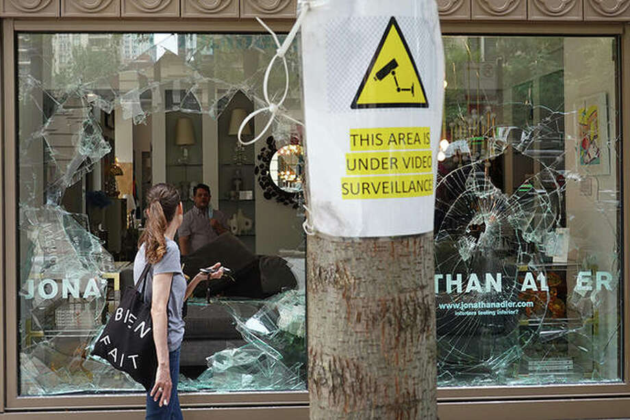 A woman looks through the shattered glass window of an interior design store that was looted in Chicago. Police made more than 100 arrests as widespread looting and disorderly conduct were reported downtown and other areas of the city. Officials believe the violence had apparently grown out of a shoot out between police and a suspect. Photo: Scott Olson | Getty Images