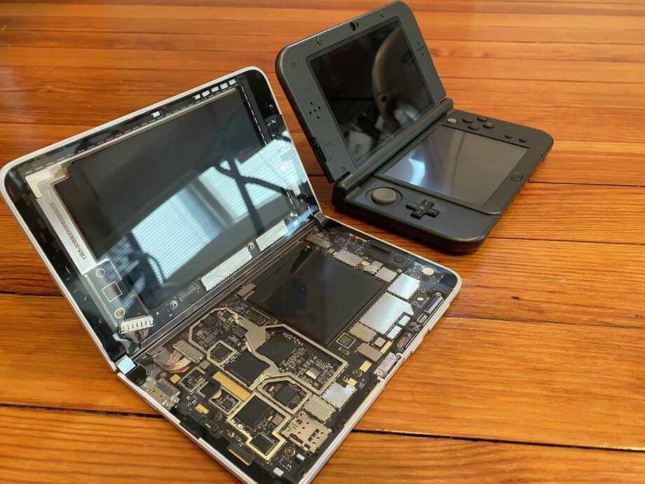 The see-through Surface Duo next to a Nintendo 3DS XL, a dual-screen device my family has used a lot. Photo: Scott Stein/CNET