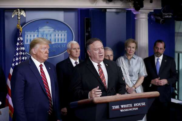 Mike Pompeo, secretary of state, canter, speaks as President Donald Trump, left, listens during a Coronavirus Task Force news conference in the briefing room of the White House in Washington D.C. on March 20, 2020.