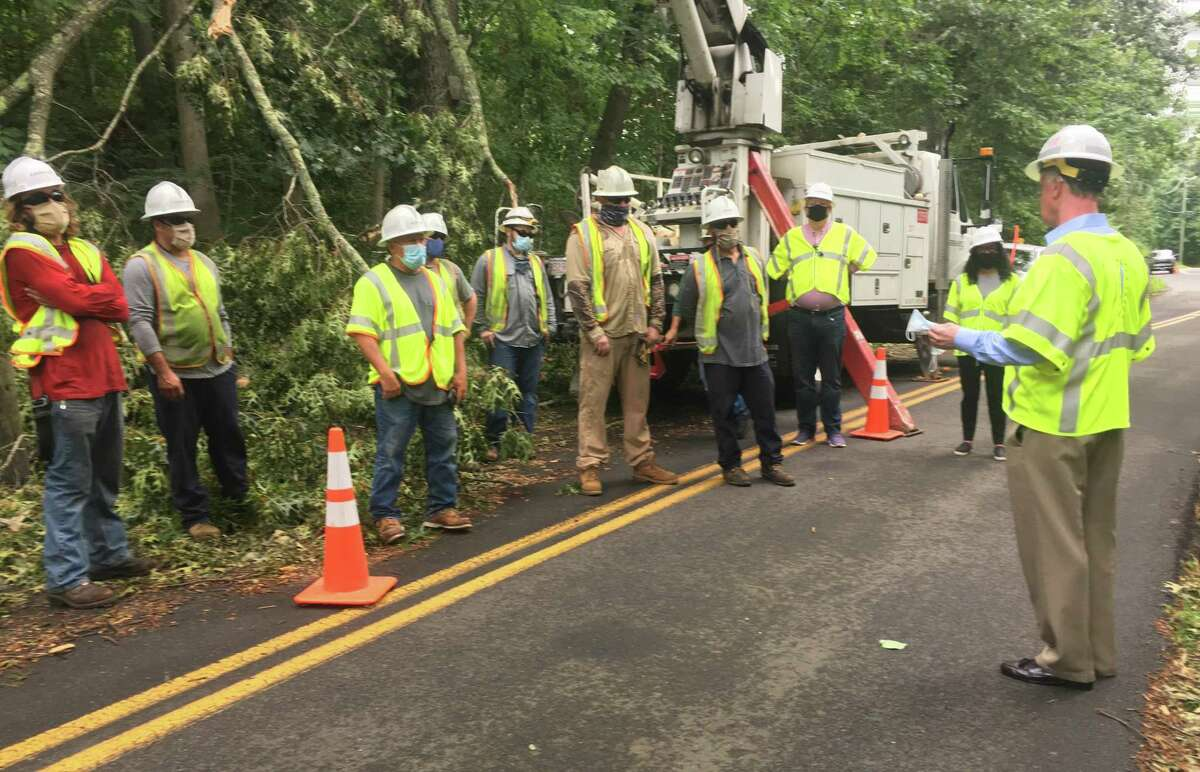 James Judge, right, visited a group of line workers during the post-Isaias storm recovery in Connecticut. Judge is chairman and CEO of Eversource, where he has been criticized for failing to be the public face of the company during an extended power failure that saw 60 percent of customers lose service.