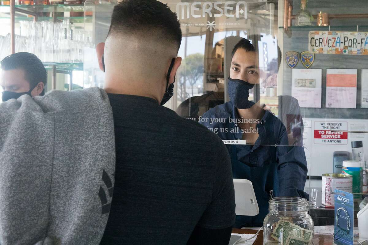 To protect against COVID-19 infection, Mansea employee Haven Tichy takes an order behind a sneeze guard from a customer at the restaurant on Treasure Island in San Francisco, California on Aug. 11, 2020.