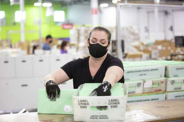 A worker wearing a protective mask places enveloped ballots into a postal service bin at the Runbeck Election Services facility in Phoenix on June 23, 2020.