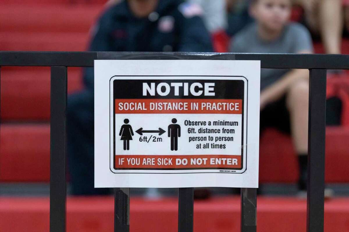Signs are posted throughout the gymnasium reminding visitors to adhere to social distancing guidelines during a non-district high school volleyball match at Hargrave High School in Huffman, Tuesday, August 11, 2020.