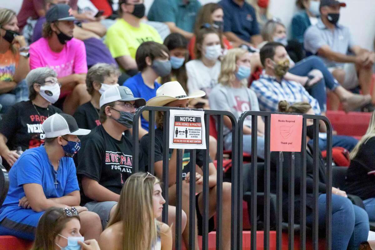 Visitors sit on bleachers during a non-district high school volleyball match at Hargrave High School in Huffman, Tuesday, August 11, 2020.