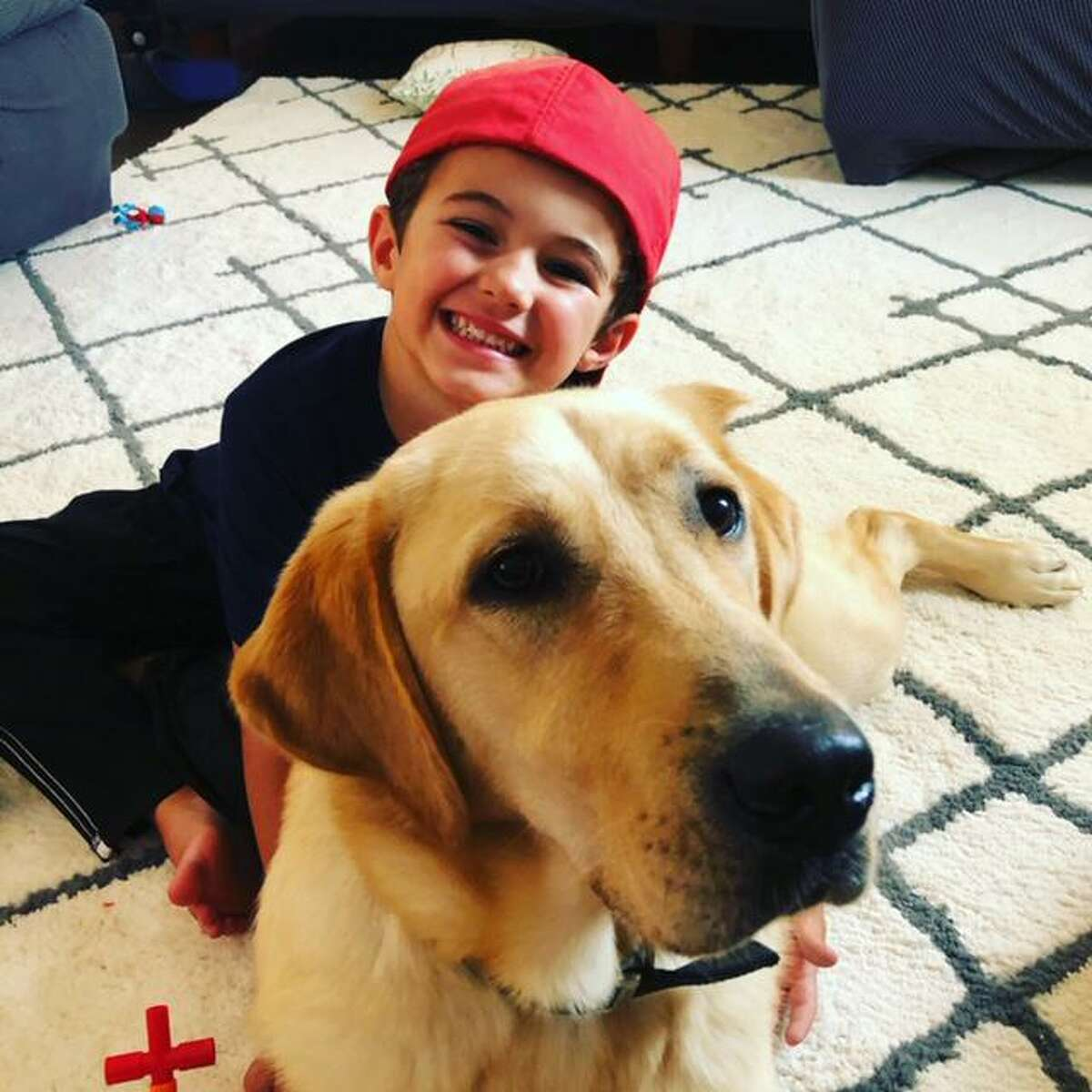 Leo Golusinski, 5, joins his service dog, Champion. Leo and his mom Lisa Halsgrove recently completed ECAD's Canine MAGIC Team Training classes and will celebrate with a virtual graduation ceremony at 6 p.m. Friday. To see the graduation, go to www.facebook.com/ECADServiceDogs