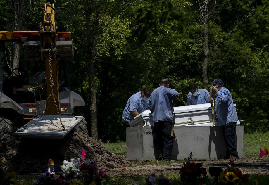 Forest Lawn Cemetery workers lower Trancito Rangel Diaz's casket during his funeral at Forest Lawn Cemetery on Aug. 4 in Houston. Rangel, 46, was a construction worker who died of COVID-19. Photo: Godofredo A. Vásquez/Staff Photographer / ? 2020 Houston Chronicle