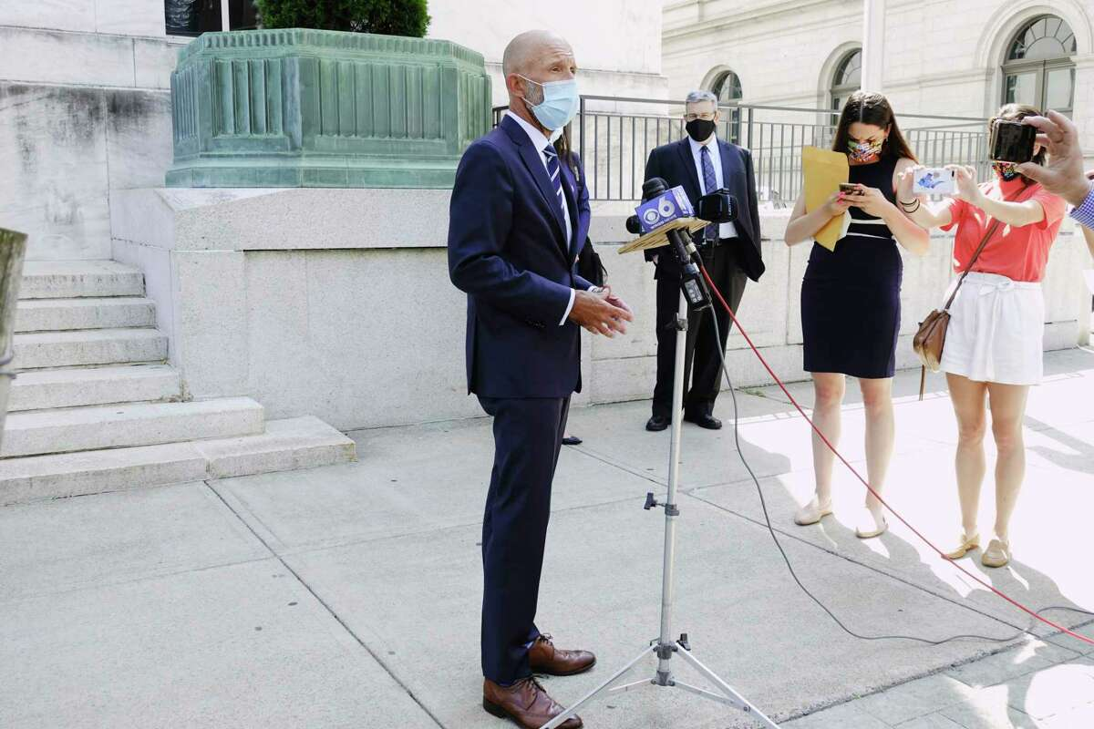 Attorney Michael Koenig speaks to members of the media as his client, Michael Mann, background, the ex-MyPayrollHR CEO, looks on outside U.S. District Court on Wednesday, Aug. 12, 2020, in Albany, N.Y. Mann was in court to plead guilty. (Paul Buckowski/Times Union)