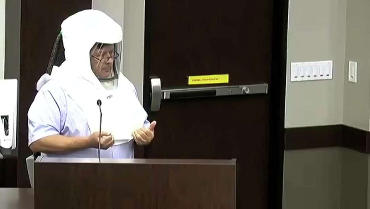 Ted McClain, who spoke in person, was wearing a hood mask similar to a hazmat suit piece as a recommendation to the board for teachers.