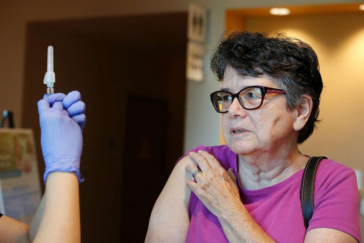 Laura Mello (right) of Milpitas, waits as her flu shot is prepared at the Kaiser Permanente Santa Clara flu clinic from June Bang (left), flu clinic LVN, on Thursday, October 3, 2019 in Santa Clara, Calif.