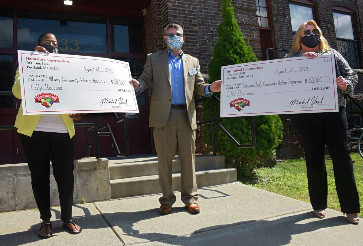 From left, Neenah Bland, Albany Community Action Partnership executive director, Andy Willette, director of operations, Hannaford Supermarkets, and Debra Schimpf, CEO, Schenectady Community Action Program, hold the checks to Hannaford Supermarkets equaling $100,000 to support Capital Region families and children impacted by COVID-19 on Wednesday, Aug. 12, 2020 in Albany, N.Y. The donation, presented in front of Albany Community Action Partnership, includes $50,000 each to Albany Community Action Partnership and Schenectady Community Action Program. (Lori Van Buren/Times Union)