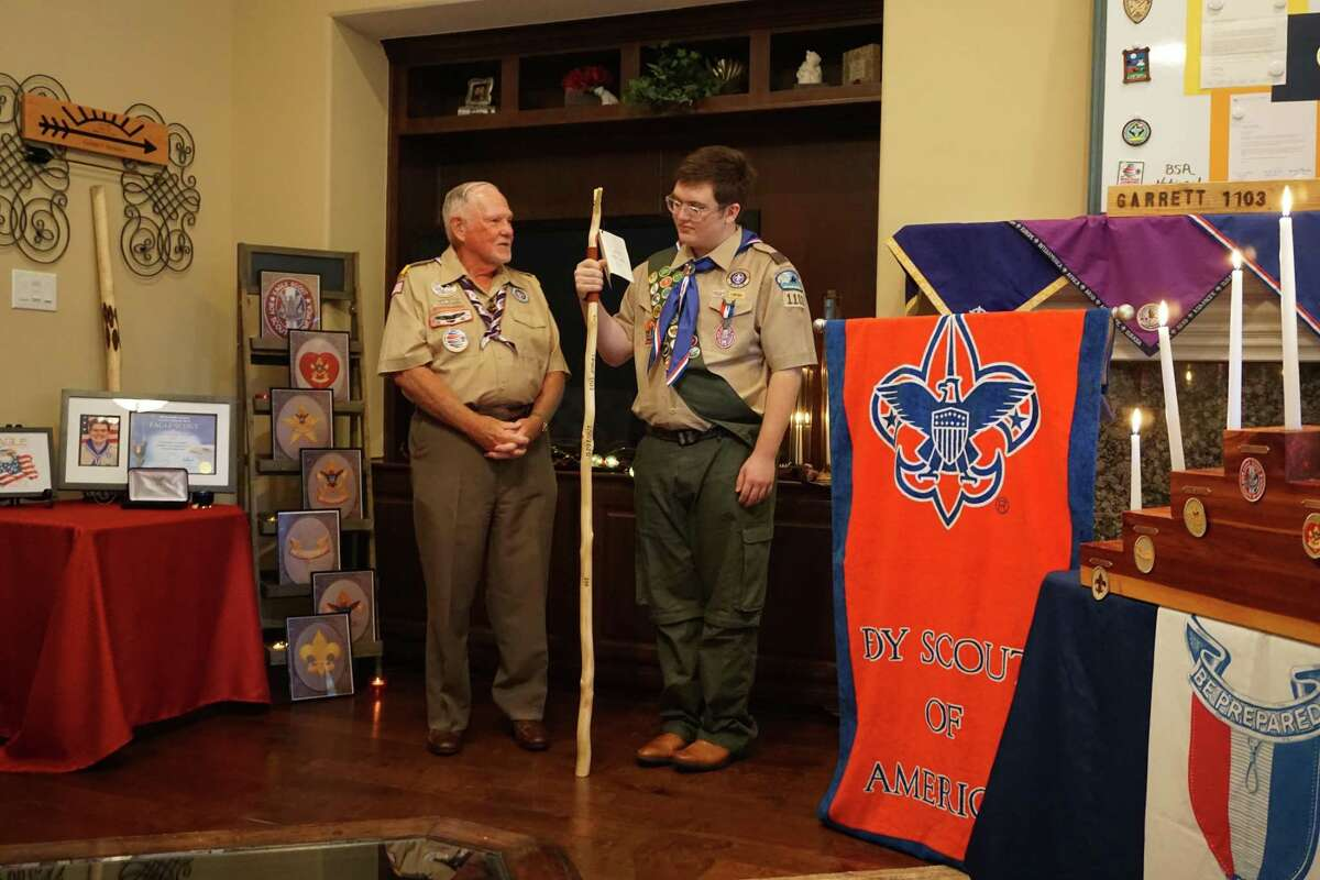 Bari Saunders, left, presents Garrett Sheroke with a special staff at his Eagle Scout Court of Honor ceremony in Katy on Saturday, Aug. 8.