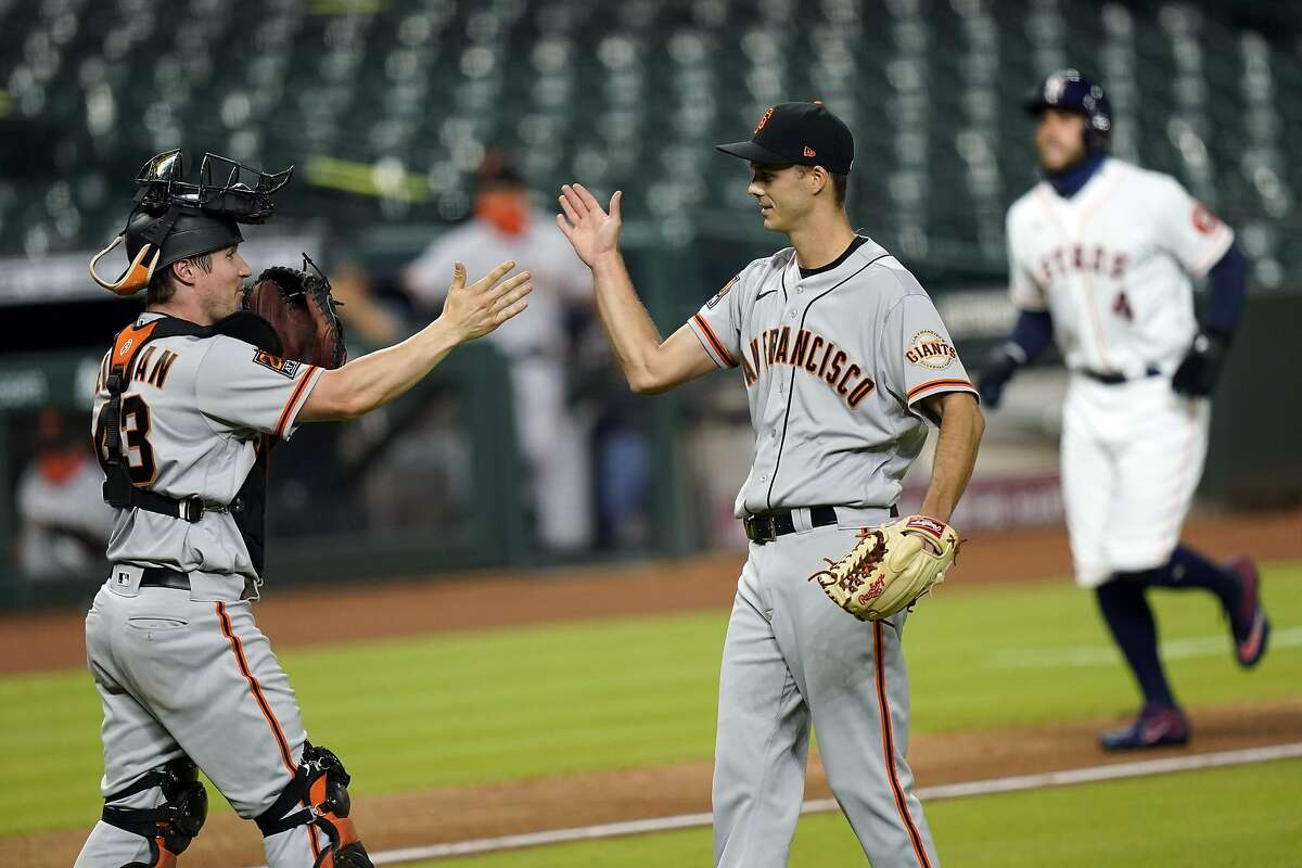 San Francisco Giants catcher Tyler Heineman (43) celebrates with relief pitcher Tyler Rogers after a baseball game against the Houston Astros Tuesday, Aug. 11, 2020, in Houston. The Giants won 7-6 in 10 innings. (AP Photo/David J. Phillip)