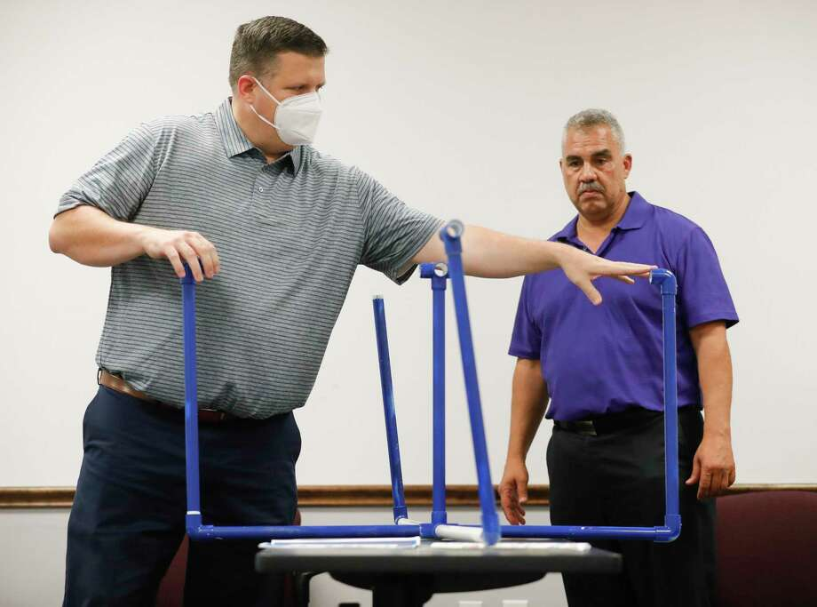 Warner Phelps, second vice president of the Conroe Noon Lions Club, shows a prototype of a safety barrier for students to use while sitting at their desks beside Club President Ralph Perez, Tuesday, Aug. 12, 2020, in Conroe. The club will construct and donate 60 plastic barriers to Conroe ISD's Reeves Elementary School. Photo: Jason Fochtman, Houston Chronicle / Staff Photographer / 2020 © Houston Chronicle