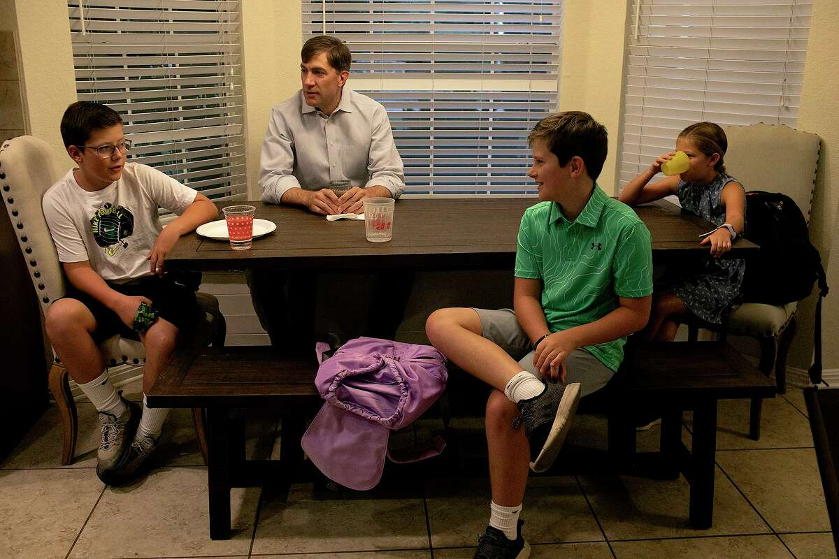 Kevin Thompson sits with his children including Cooper, 12, from left, and twins Tucker and Elizabeth, 10, as they prepare for the first day of school in Boerne on Wednesday.