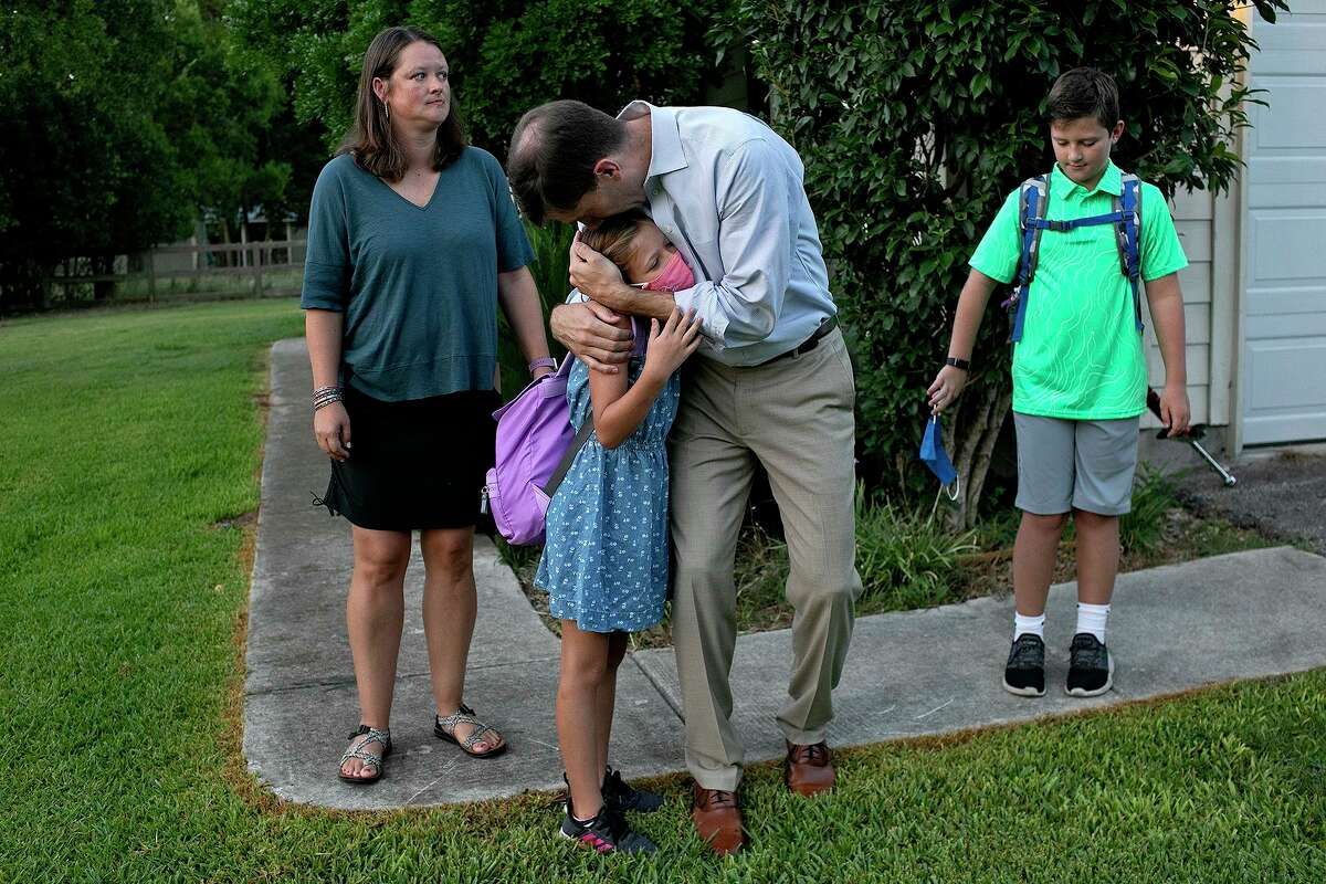 Kevin Thompson hugs his daughter, Elizabeth, 10, goodbye, next to her twin brother, Tucker, as their mother, Sarah Thompson, waits to walk them to Curington Elementary School for their first day of fourth grade in Boerne on Wednesday.