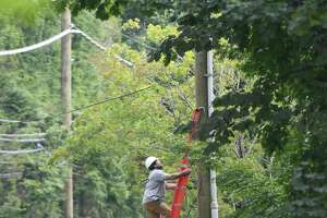 A lineman works on a power line on Riversville Road in Glenville Wednesday.   section of Greenwich, Conn. Wednesday, Aug. 12, 2020. While power has been restored to most Greenwich residents since Tropical Storm Isaias hit last Tuesday, a small number still remain without power.