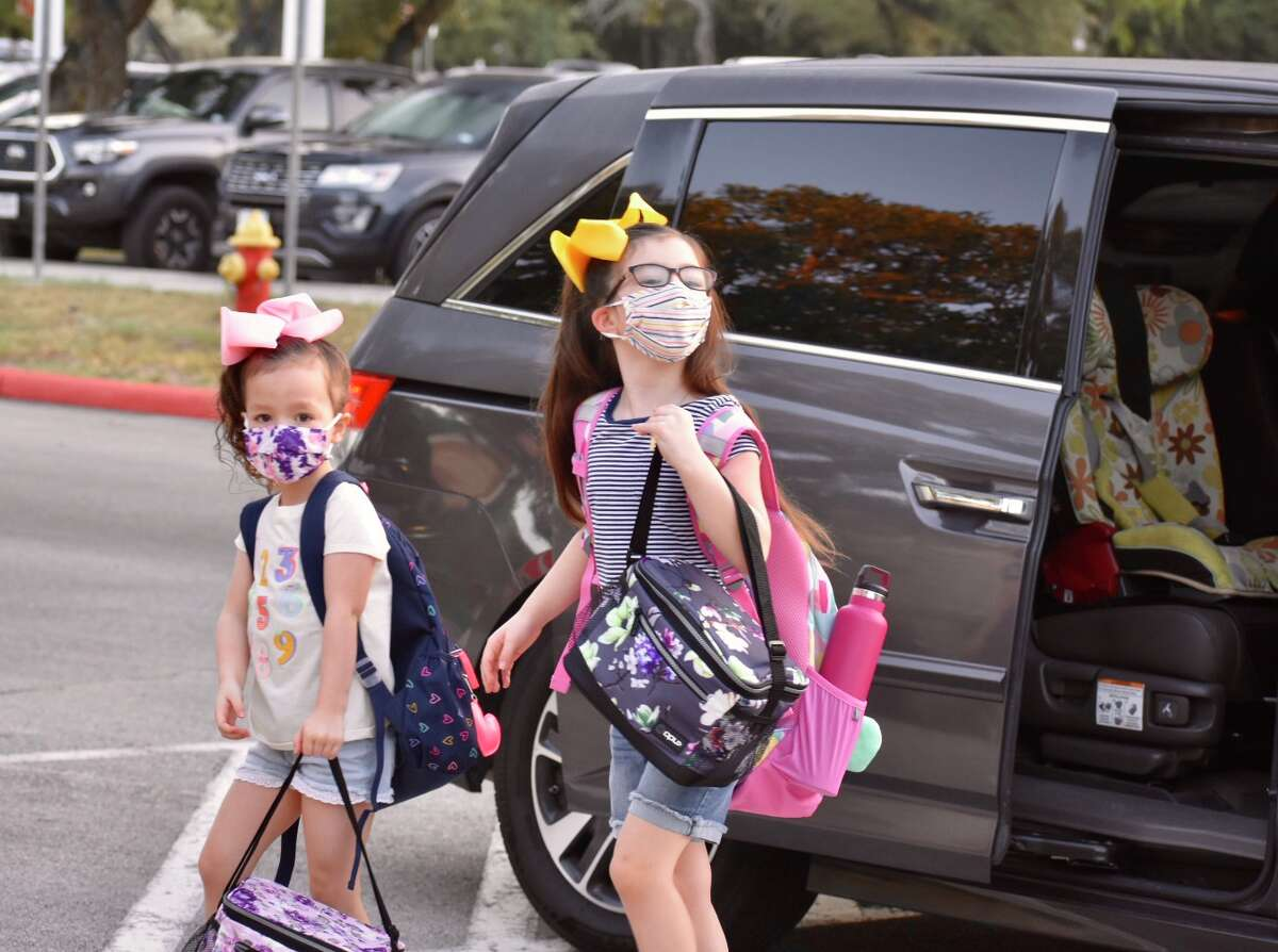 Two students walk into school with masks on their first day of class.
