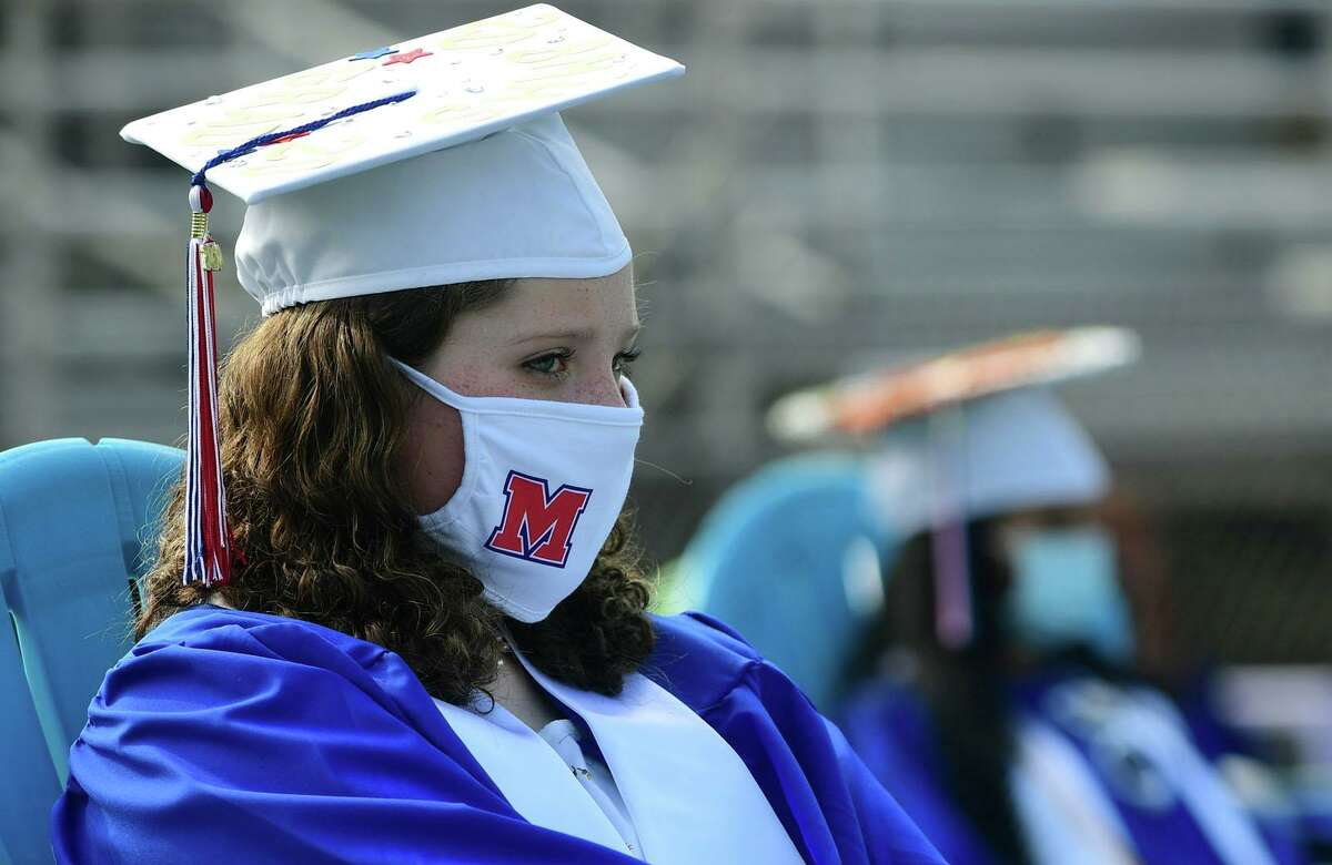 Graduates with the Brien McMahon High School Class of 2020 including Anna Burley attend one of several small commencement ceremonies Wednesday, August12, 2020, on the football field at the school in Norwalk, Conn.