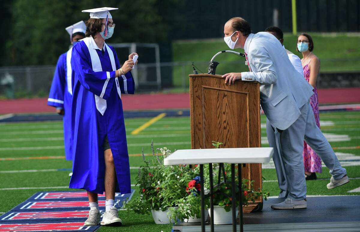 Principal Scott Hurwitz reads the names of graduates with the Brien McMahon High School Class of 2020 as they attend one of several small commencement ceremonies Wednesday, August12, 2020, on the football field at the school in Norwalk, Conn.