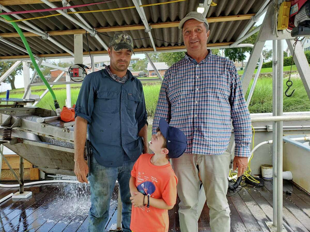 Norm Bloom with his son, Jim, captain of The Cultivator, and grandson Jack as they were washing off seed oysters at their one-of-a-kind oyster nursery in Norwalk.