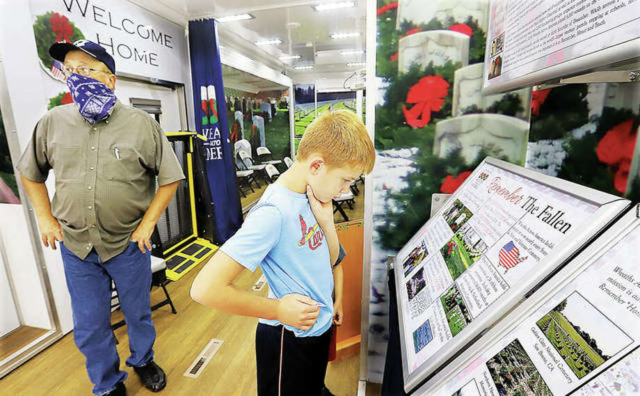Jim Mager of Godfrey, left, listens to a guide talk about the Wreaths Across America Mobile Education Exhibit Wednesday as his grandson, Josh Cordes, 10, right, reads one of the exhibits inside the large traveling museum. The education exhibit made a stop in Alton Wednesday. Alton participates in the annual Wreaths Across America event each December at the Alton National Cemetery.