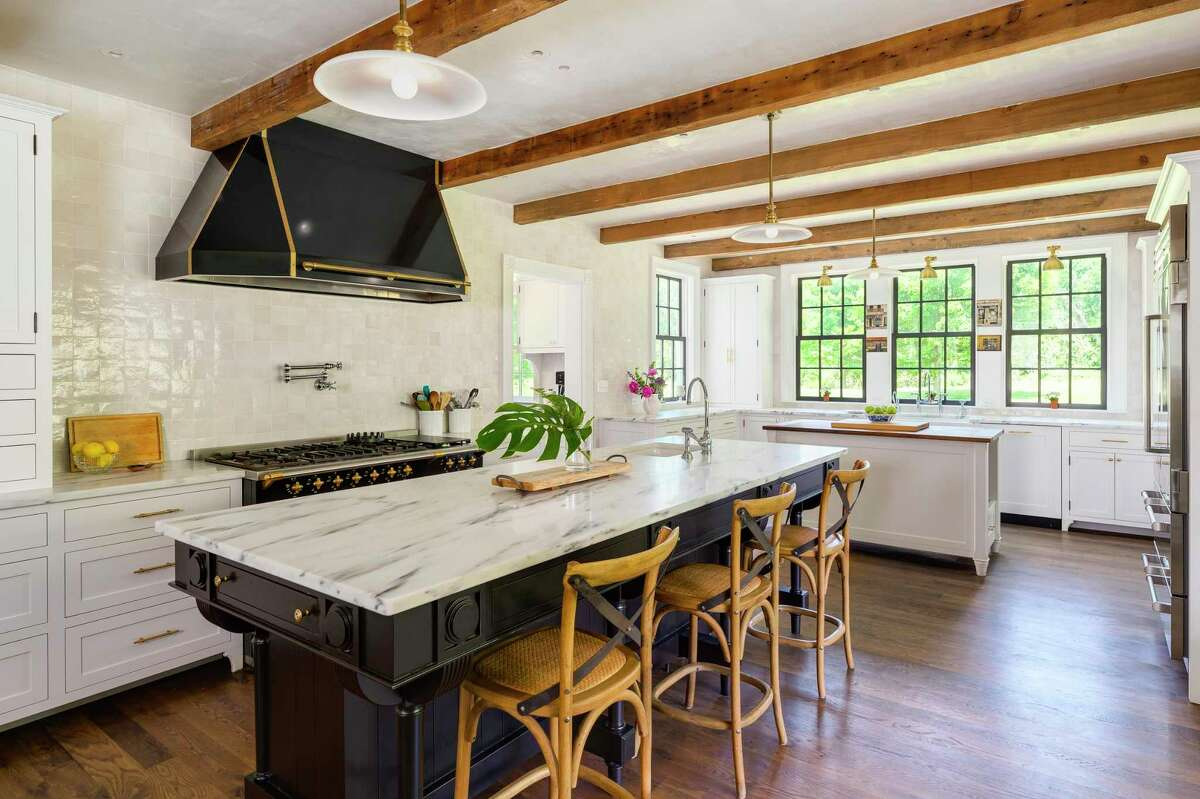 The gourmet kitchen features Danby Vermont marble counters, custom cabinetry, imported hand-made tile backsplash, two islands, farm sink, character oak flooring, and a Lacanche range with a pot-filler.